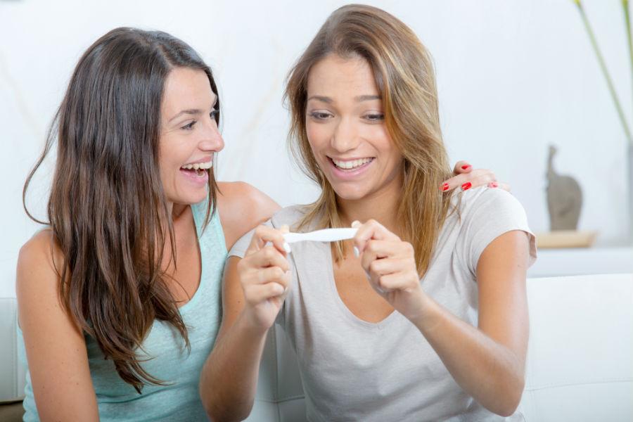 Due amiche guardano felici un test di gravidanza positivo