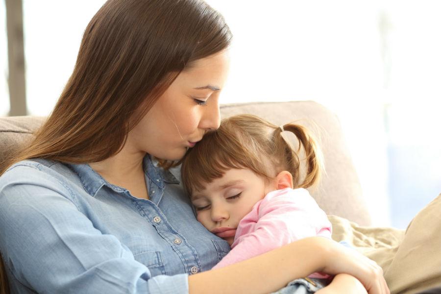 Mamma coccola la sua bambina sul divano
