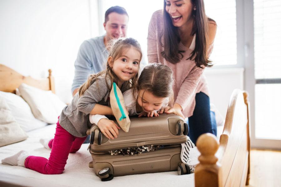 Mamma, papà e due bambini cercano di chiudere una valigia stracolma