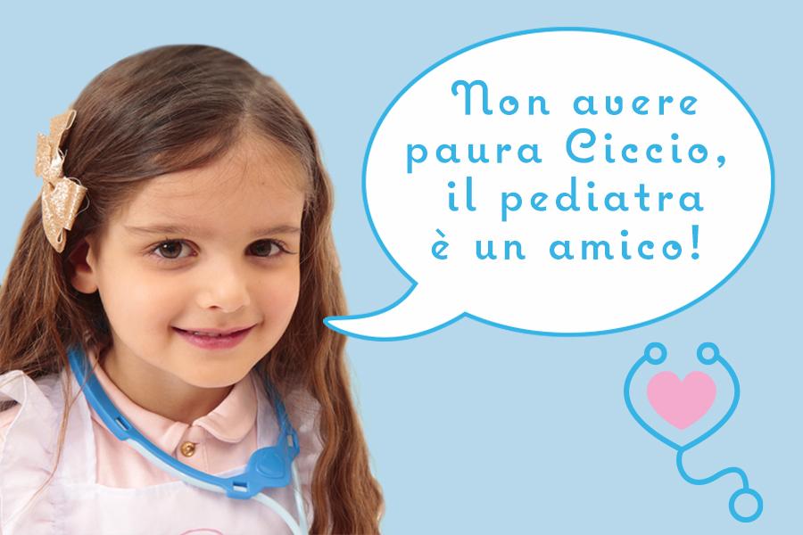 """Bambina con stetoscopio giocattolo e frase """"non avere paura Cicciobello, il pediatra è un amico"""""""