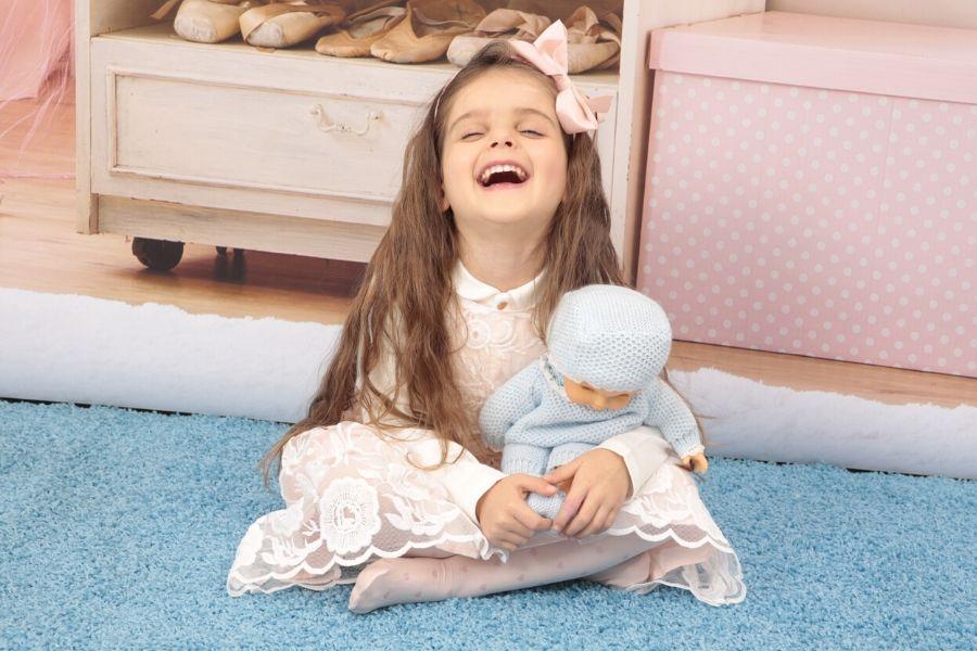 Cicciobello Angelo Azzurro sulle gambe di una bambina che ride sentendo le letture animate