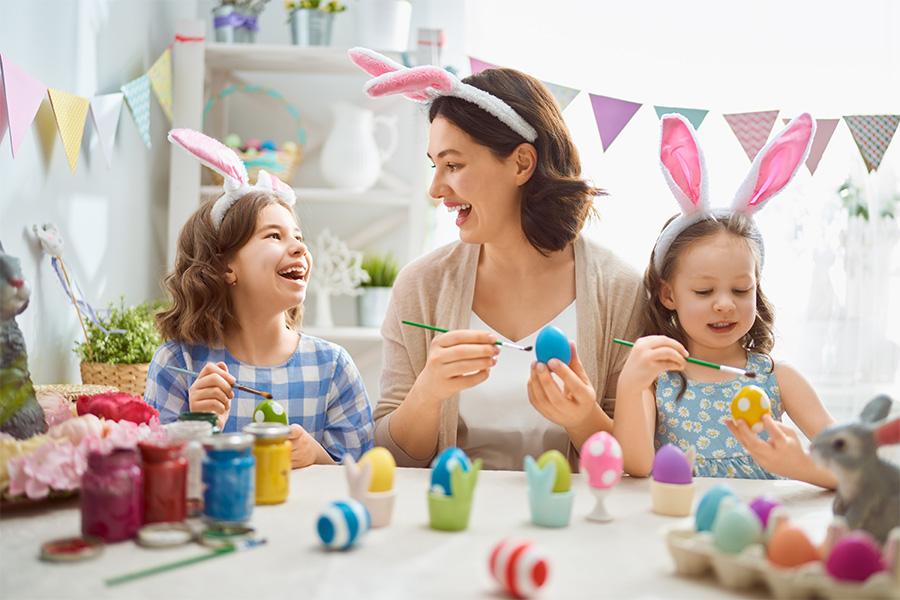 Mamma e figlie decorano le uova per la caccia alle uova di Pasqua