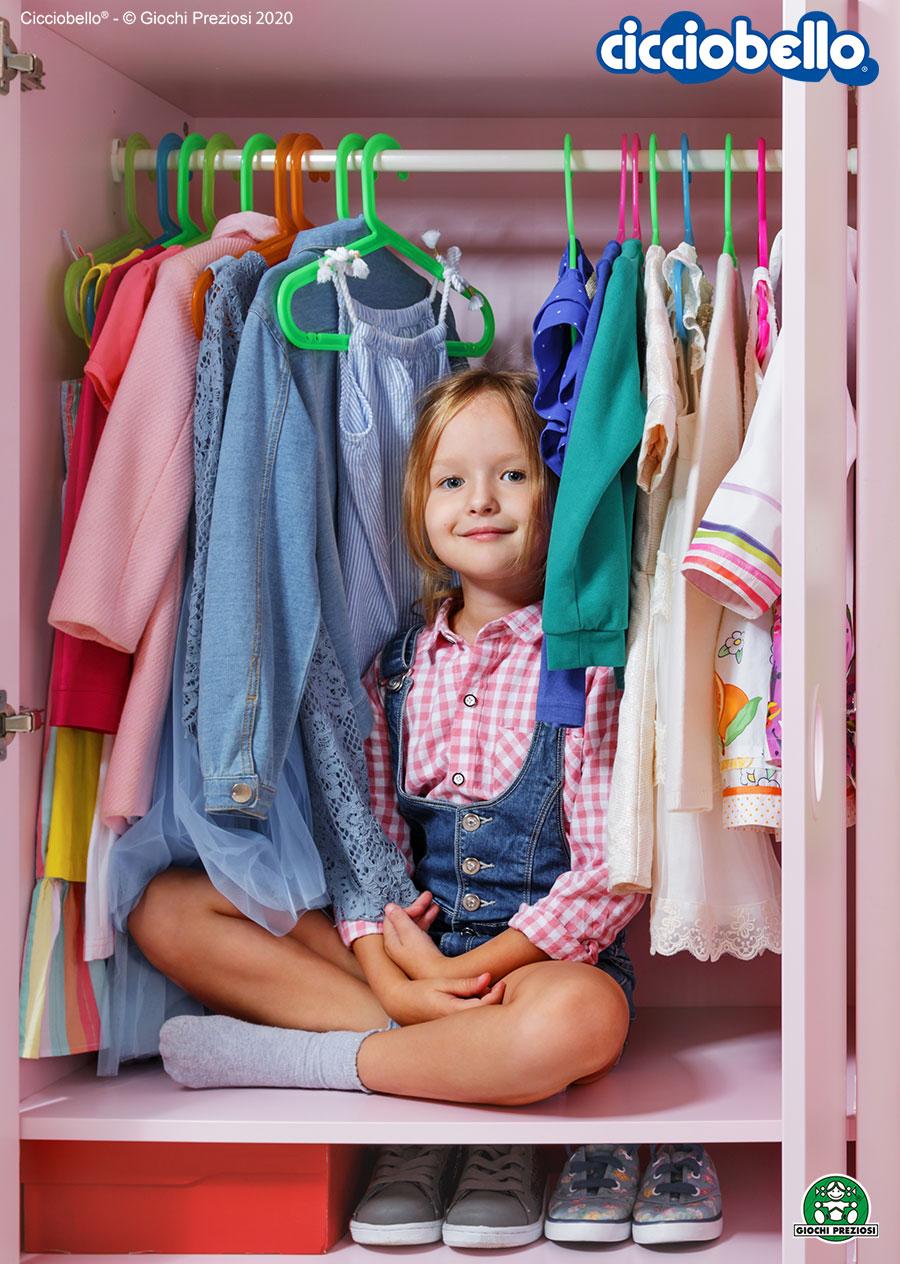 Bambina seduta sorridente all'interno del suo armadio
