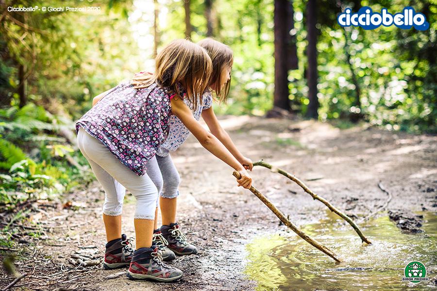 Due bambine giocano sulla riva di un ruscello