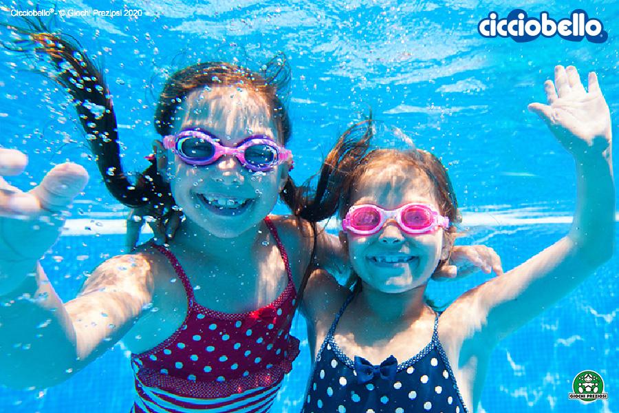 Due bambini fotografate dentro l'acqua in una piscina